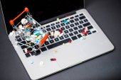 Fotografie laptop and pills in small shopping trolley