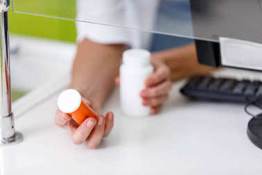 pharmacist holding containers with medication