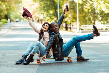 couple sitting on longboard with hats in hands