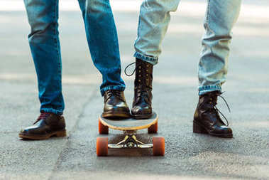 couple standing together on one longboard