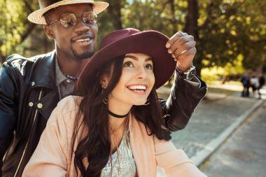 Boyfriend touching girlfriends hat