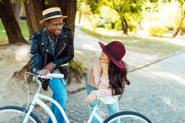 Lovely interracial couple standing and leaning on a bike stock vector