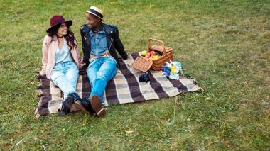 multicultural couple sitting on blanket