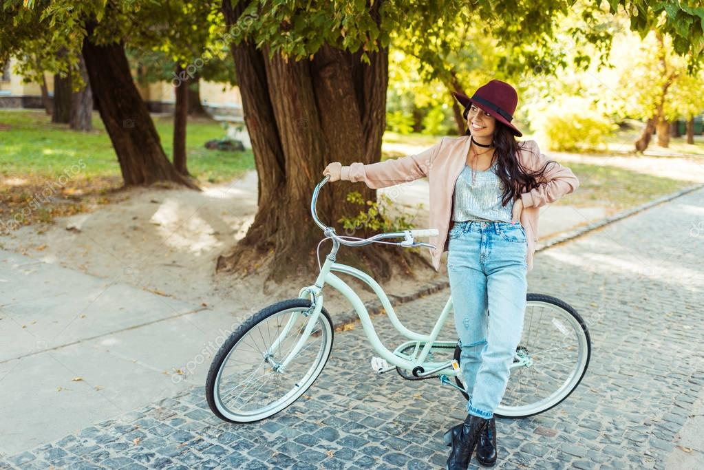 woman in hat standing with bicycle