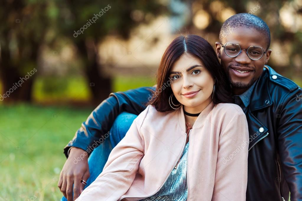 multicultural couple sitting on grass