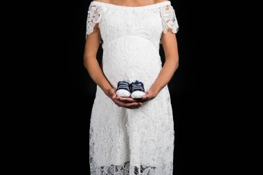 pregnant woman holding pair of shoes