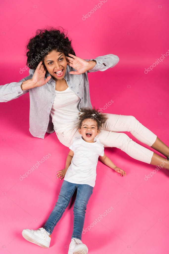 Mother and daughter screaming and sitting on floor