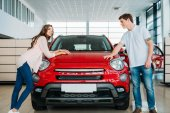 Couple leaning on red car in showroom