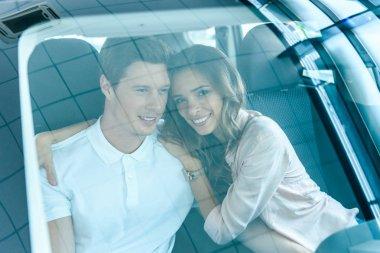 Happy couple sitting in car salon