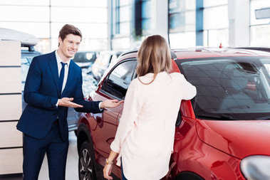 Manager inviting customer sit into car