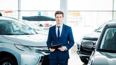 manager standing between cars in showroom