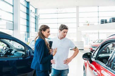 Sales manager describing car to customer in showroom stock vector