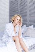 Fotografie zamyšlený mladá žena v županu, seděl na posteli se zavřenýma očima