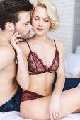 Fotografie sexy junge Frau in Dessous, die hübschen Freund am Bett zu berühren