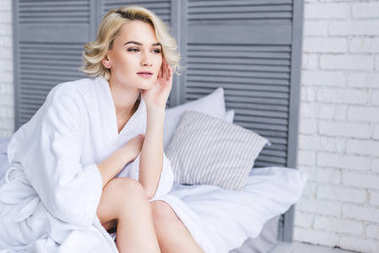 pensive blonde girl in bathrobe sitting on bed and looking away