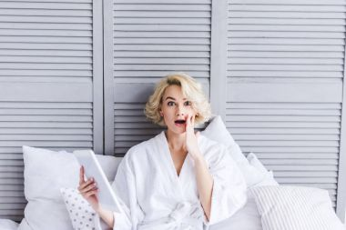 shocked young woman in bathrobe holding digital tablet and looking at camera in bedroom