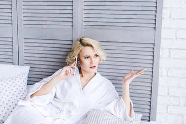 serious young woman in bathrobe looking away and talking by smartphone while lying on bed