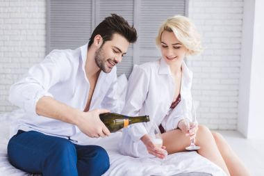handsome smiling young man pouring champagne into glasses while sitting with girlfriend on bed
