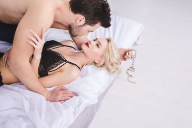 young lovers with handcuffs lying together in bed