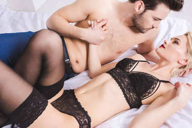 beautiful young couple looking at each other and holding hands in foreplay on bed