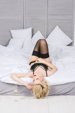 seductive young woman in lace lingerie lying on bed with glass of champagne on floor