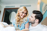 smiling couple with books in bed looking at each other