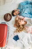 Blick aus der Vogelperspektive auf ein Touristenpaar, das im Hotelzimmer auf dem Bett liegt