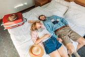 vista di alto angolo di coppia di turisti che si trovano sul letto nella camera dalbergo