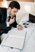 thoughtful businessman lying on bed in hotel room and looking at notebook