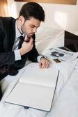 Fotografie promyšlené podnikatel ležící na posteli v hotelovém pokoji a při pohledu na notebook