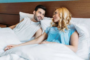 heterosexual couple holding hands in bed and looking at each other
