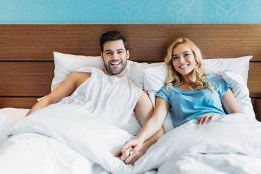 smiling heterosexual couple holding hands in bed