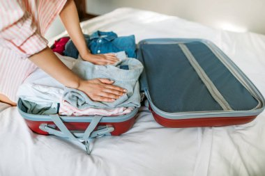 cropped image of girl packing travel bag for weekend