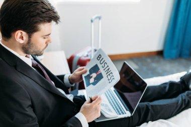 businessman reading newspaper in hotel room