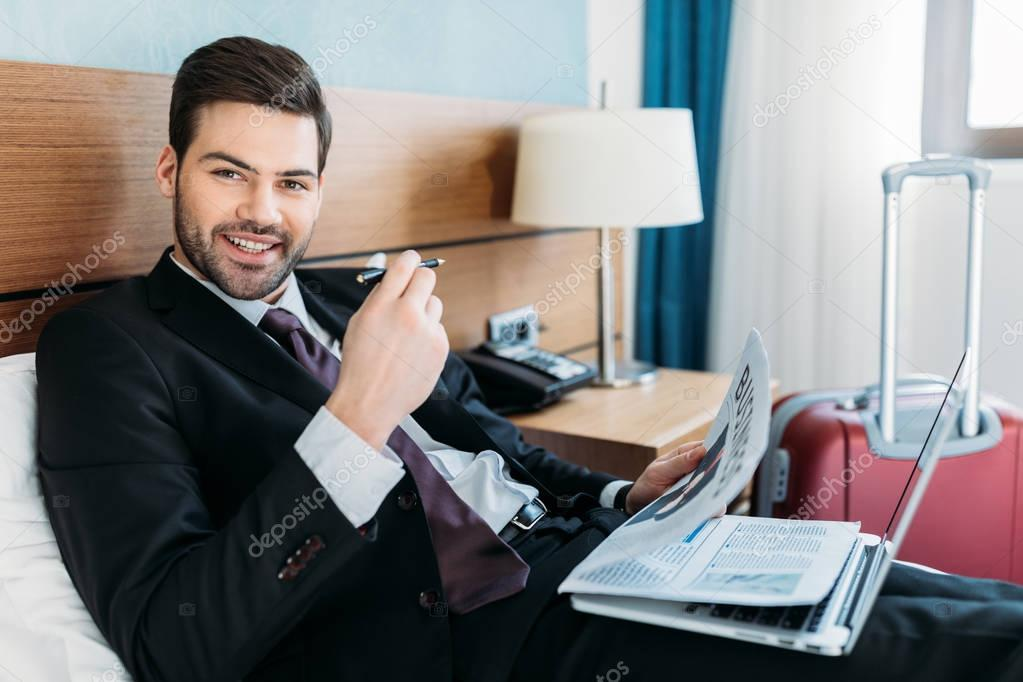 smiling businessman holding newspaper and looking at camera