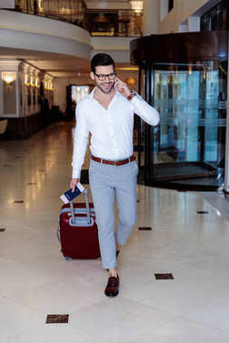 handsome traveler walking in hotel and talking by smartphone