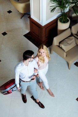 overhead view of smiling couple of travelers walking with luggage in hotel