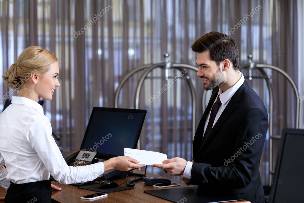 smiling receptionist giving envelope to businessman in hotel