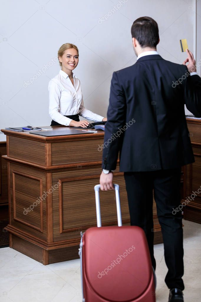 rear view of businessman showing credit card to receptionist in hotel