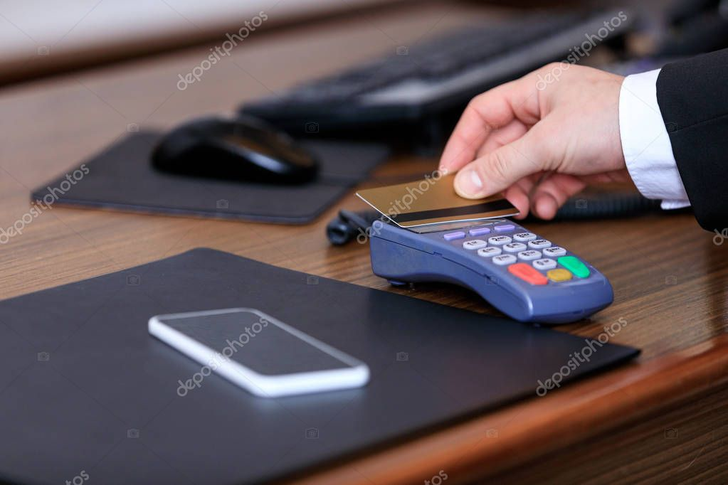 cropped image of businessman paying with credit card in hotel