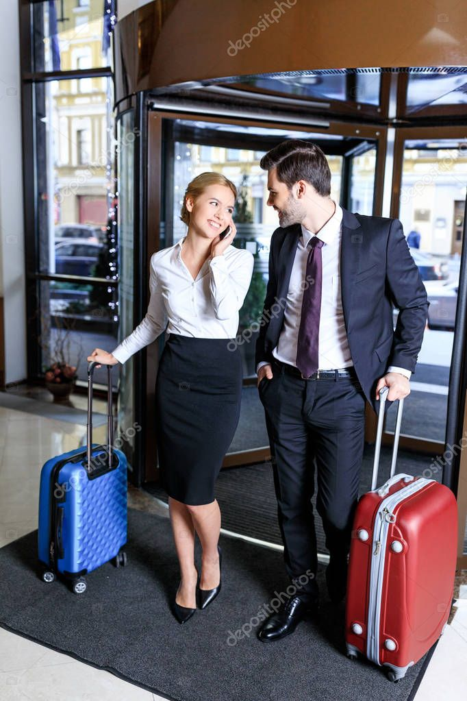 businesswoman entering hotel and talking by smartphone