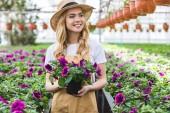 Fotografie Mladé samice zahradník drží Květináč s květinami ve skleníku