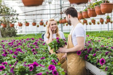Young male gardener holding pot with flowers while woman talking on phone