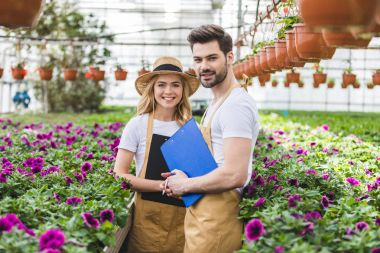 Couple of gardeners holding clipboards by flowers in greenhouse