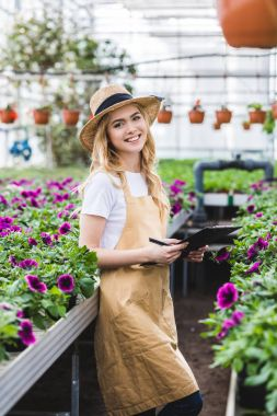 Blonde woman with clipboard filling order of flowers in greenhouse