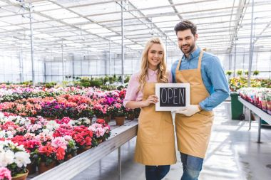 Male and female owners of glasshouse holding Open board by flowers