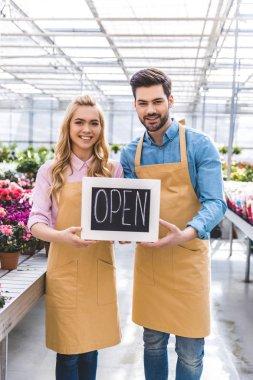 Couple of gardener holding Open board by flowers in greenhouse