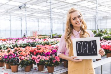 Blonde woman holding Open board by flowers in greenhouse
