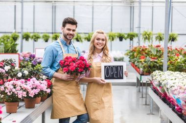 Young man and blonde woman holding Open board by flowers in glasshouse