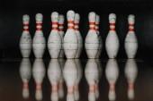 Fotografia perni di bowling grungy in cancello con la riflessione in pavimento lucido
